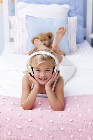 Smiling little girl lying in bed listening to the music photo