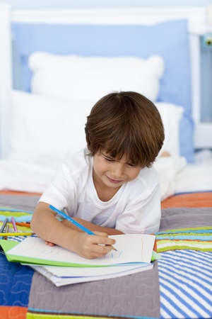 Little boy drawing in bed photo