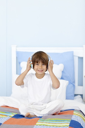 Little boy listening to music in his bed Stock Photo - 10244790