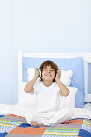 Little boy listening to music on headphones in his bed photo