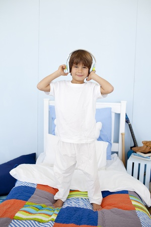 Little boy with headphones on dancing in bedroom photo