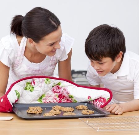 ni�os cocinando: Madre e hijo mirando las galletas hechas en casa