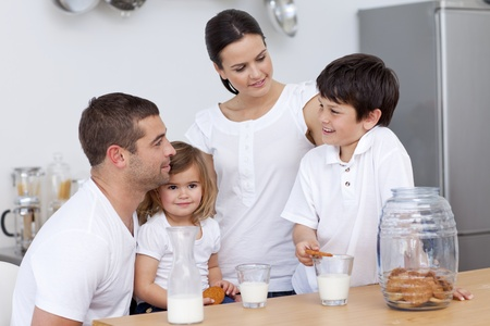 ni�os comiendo: Los padres y los ni�os comer galletas y leche de consumo Foto de archivo