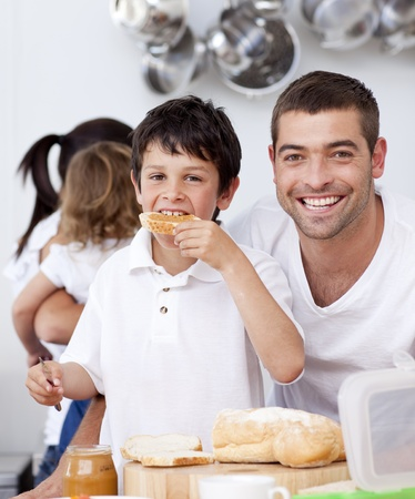 Father and son eating a toast in breakfast time photo