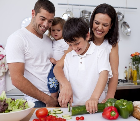 family health: Cute boy preparing food with his family