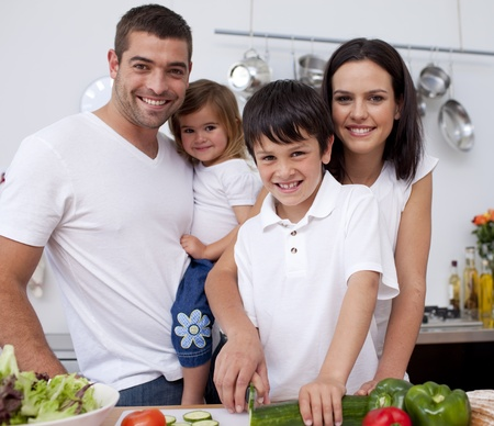 Young boy preparing food with his family photo
