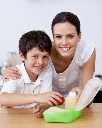 lunchen: Lachende moeder en zoon maken de school lunch