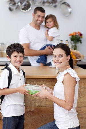 Radiant mother giving food to her son for lunch Stock Photo - 10259389