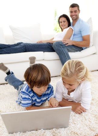 Children using a laptop and couple lying on sofa photo