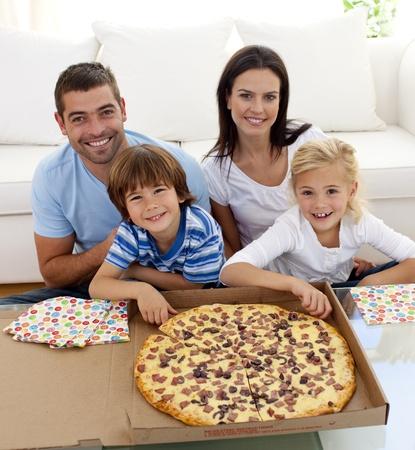 familia comiendo: Familia comiendo pizza en sof� Foto de archivo