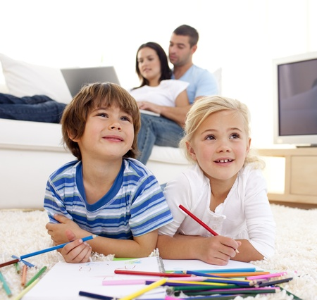 lying on floor: Children painting in living-room and parents on sofa