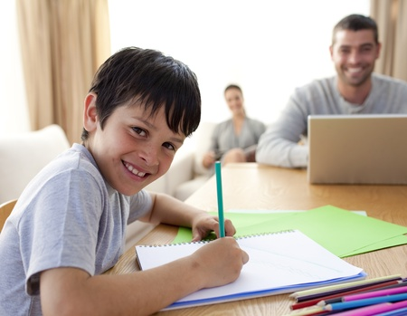 Boy painting and parents working at home Stock Photo - 10256599