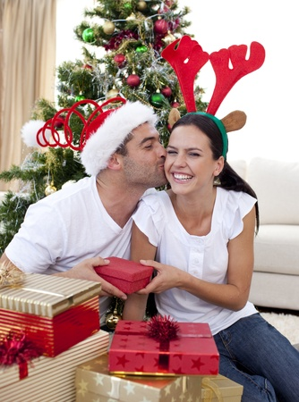 Smiling couple giving presents for Christmas photo