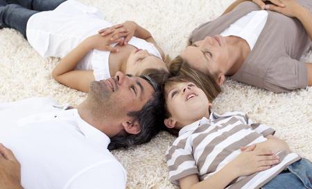 girotondo bambini: Famiglia sdraiato sul pavimento a casa con teste insieme