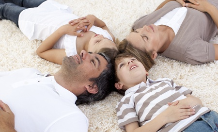 Family lying on floor at home with heads together photo