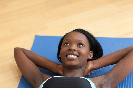 situp: Smiling woman in gym clothes doing sit-ups