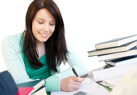 Smiling teen girl studying on a desk photo