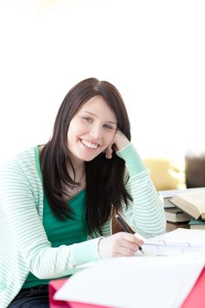 Smiling brunette student doing her homework photo