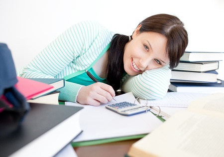 Smiling student doing her homework on a desk Stock Photo - 10257058