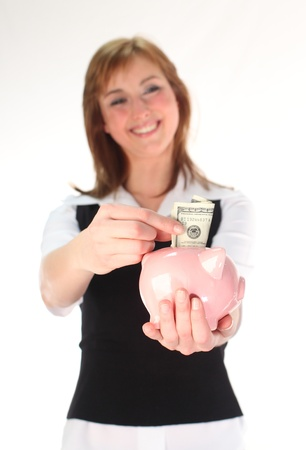 Woman putting money in a Piggy Bank in a time of recession Stock Photo - 26719163