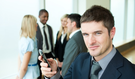 Happy businessman sending a text in office photo