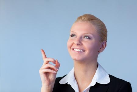 Happy Businesswoman pointing upwards photo