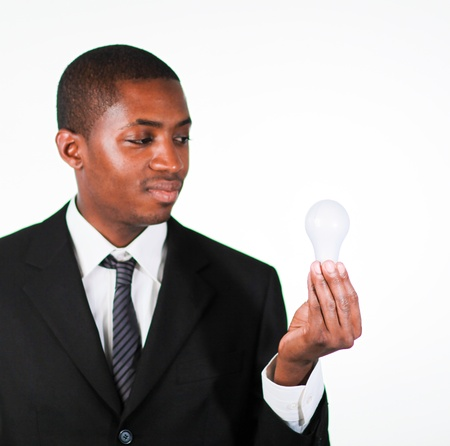 Confident businessman looking at a light bulb Stock Photo - 10234261