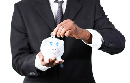 Close-up of an Young Afro-American businessman putting money in his piggy bank photo