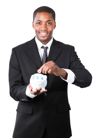 Young Afro-American businessman putting money in his piggy bank and smiling at the camera Stock Photo - 10247191