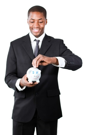 Happy Afro-American businessman putting money in his piggy bank photo