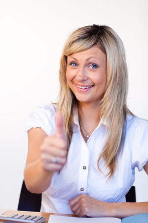 Beautiful businesswoman with thumbs up in office Stock Photo - 10250431