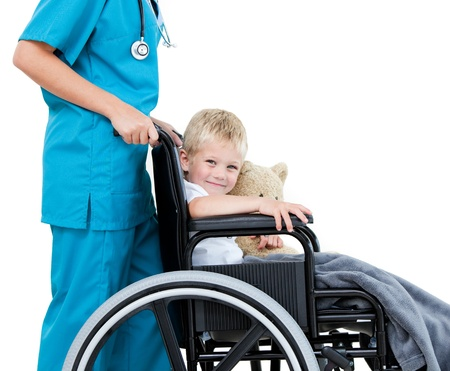 helping children: Bright female doctor carrying adorable little boy with his teddy bear in the wheelchair at the hospi