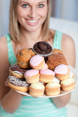Smiling woman holding a plate of cakes  photo