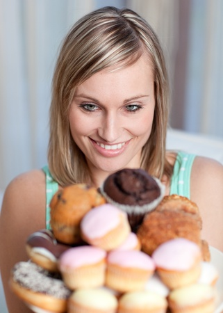 Charming woman holding a plate of cakes  photo