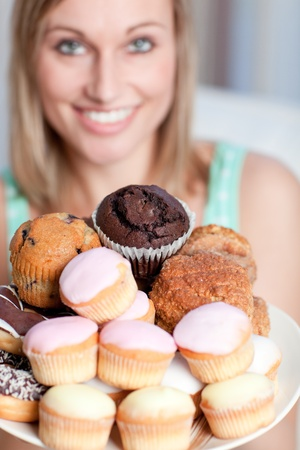 Happy woman holding a plate of cakes  photo