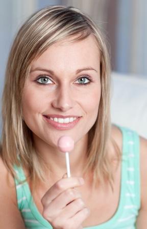 Radiant woman holding a lollipop photo