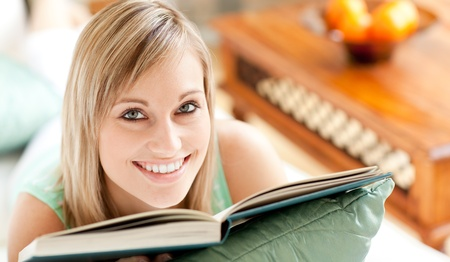 Happy woman lying on a sofa reading a book  photo