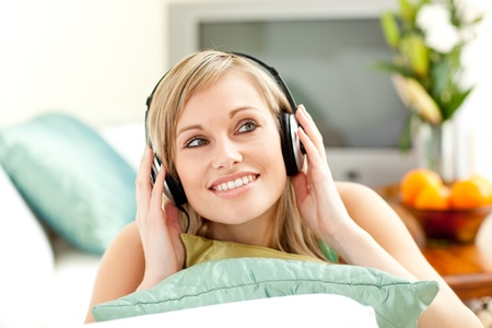 delighted: Charming blond woman listening music lying on a sofa