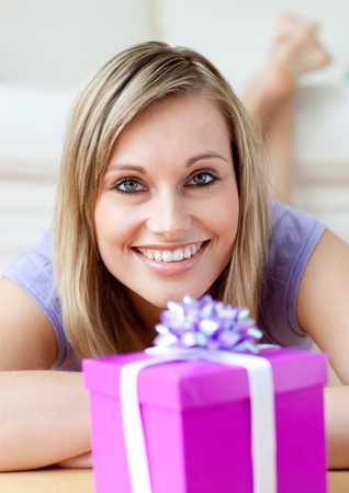 gift parcel: Cheerful woman looking at a gift