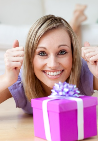 Excited woman looking at a gift lying on the floor photo