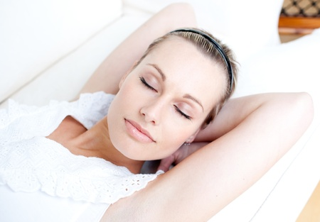 Relaxed woman lying on sofa photo