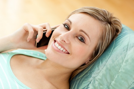 Happy young woman talking on phone lying on a sofa photo