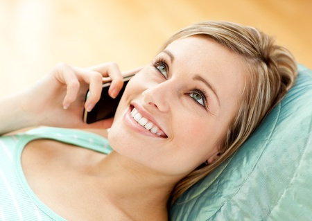 Jolly young woman talking on phone lying on a sofa  photo