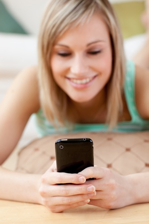 Pretty blond woman sending a text lying on the floor photo