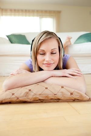 escuchando musica: Escucha música de hermosa mujer tirada en el suelo Foto de archivo