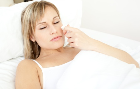 Portrait of a sick beautiful woman lying on a bed Stock Photo - 10247125