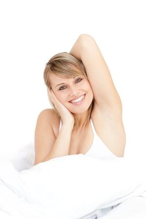 levantandose: Mujer radiante se extiende mientras que levantarse por la ma�ana Foto de archivo