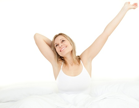 woman stretching: Delighted woman stretching sitting on her bed in the morning