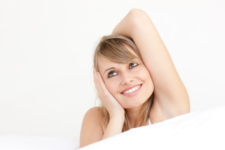 Delighted woman stretching sitting on her bed  photo