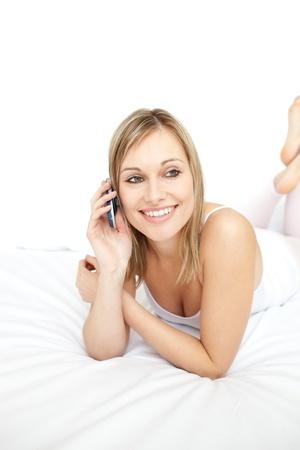 Beautiful woman talking on phone lying on her bed Stock Photo - 10250423